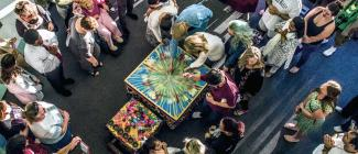 Group of people gathered around a sand mandala